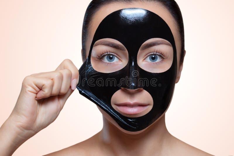 Una máscara negra a la cara de una mujer hermosa imagen de archivo
