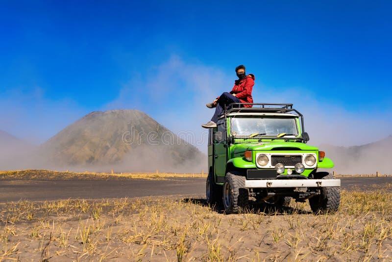Una máscara que lleva del hombre asiático y el sentarse en el coche del jeep en el soporte Bromo Un volcán activo, una de las atr fotos de archivo libres de regalías