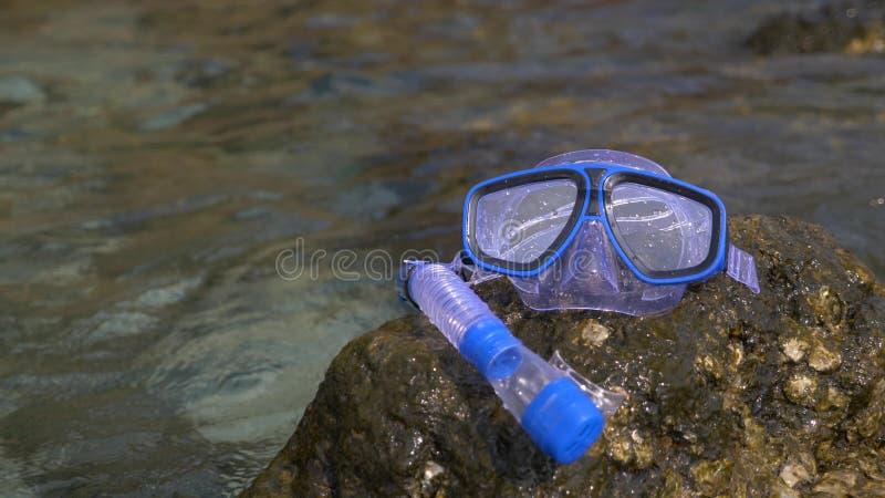 Una máscara y un tubo respirador en la playa cerca del mar fotos de archivo libres de regalías