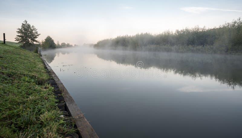 Una mañana brumosa en el agua imagen de archivo