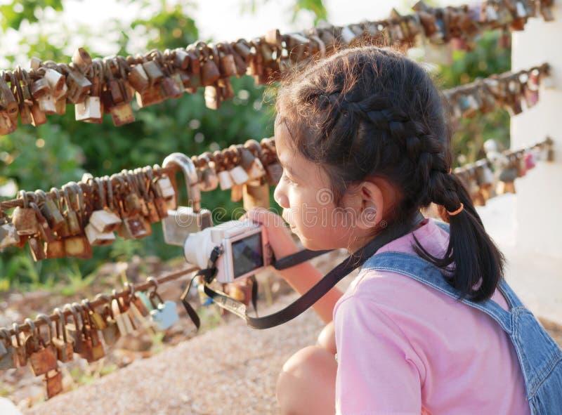 Una macchina fotografica della tenuta della bambina con la presa dell'immagine Bambino asiatico che fa viaggio della foto fotografie stock libere da diritti