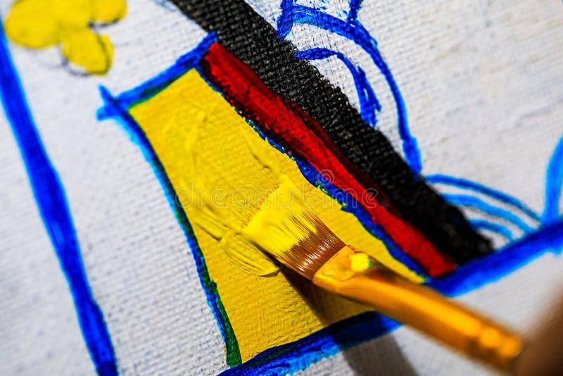 Una macro immagine di un artista che dipinge una regina della carta da gioco dei cuori su una tela nel loro studio Ciò molto dett fotografia stock