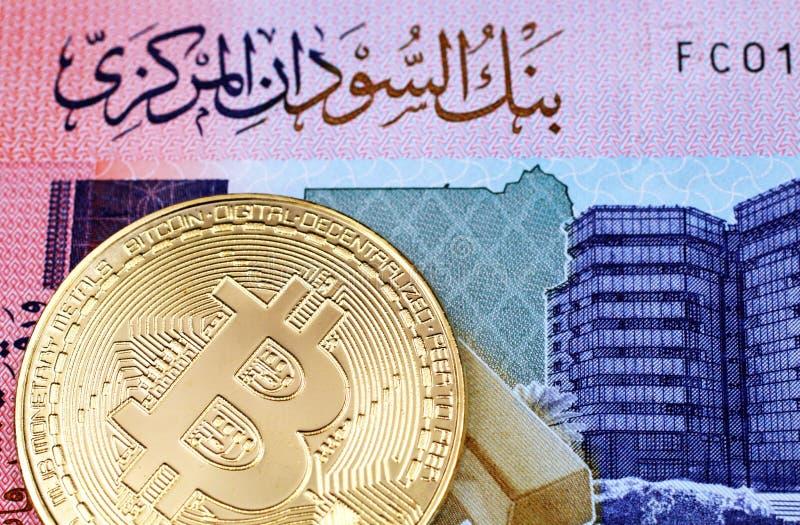 Una macro immagine di un bitcoin fisico dell'oro con una nota sudanese da cinquanta libbre fotografia stock libera da diritti