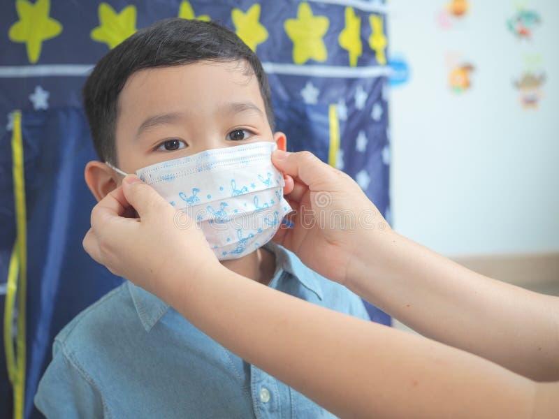 Una madre che indossa maschera protettiva per il suo bambino fotografie stock
