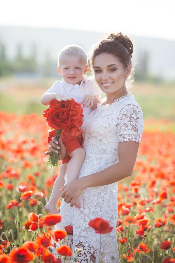 Una madre feliz con un pequeño hijo en sus brazos en el campo sin fin de amapolas rojas en un día de verano soleado foto de archivo libre de regalías