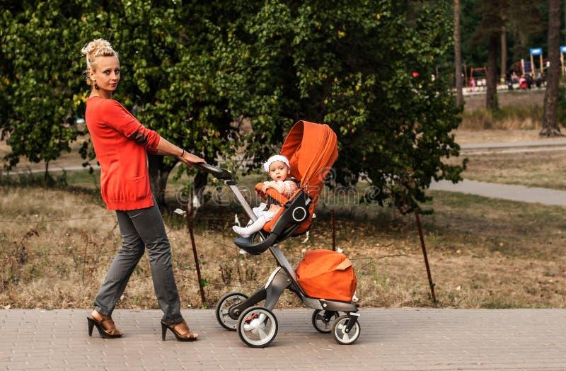 Una madre graziosa cammina nel parco e porta un passeggiatore arancio con una neonata fotografia stock