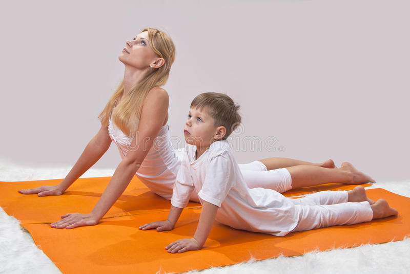 Una madre hermosa practica yoga con su hijo imágenes de archivo libres de regalías