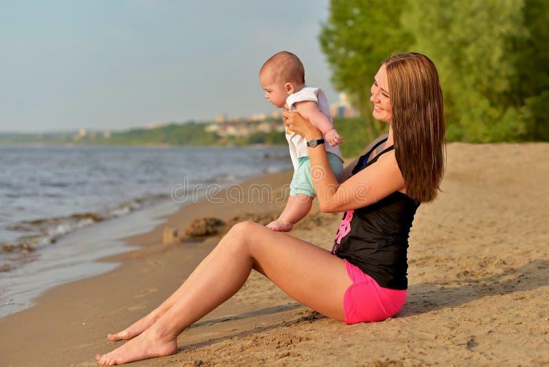 Una madre joven con una pequeña hija se está sentando en una playa arenosa fotografía de archivo