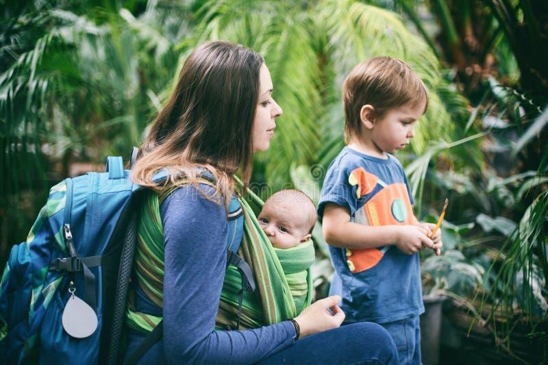 Una madre joven con un bebé en una honda y un niño pequeño está caminando en la selva imagen de archivo