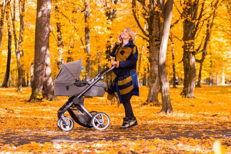 Una madre joven con un cochecito está hablando en su teléfono móvil mientras que camina en el parque fotografía de archivo libre de regalías
