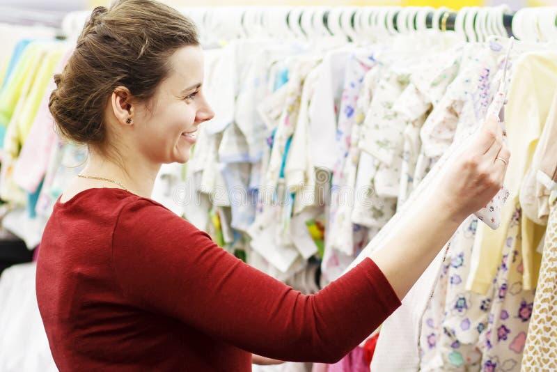 Una madre joven elige la ropa para su bebé en una tienda del ` s de los niños La muchacha elige la ropa en la alameda fotografía de archivo libre de regalías