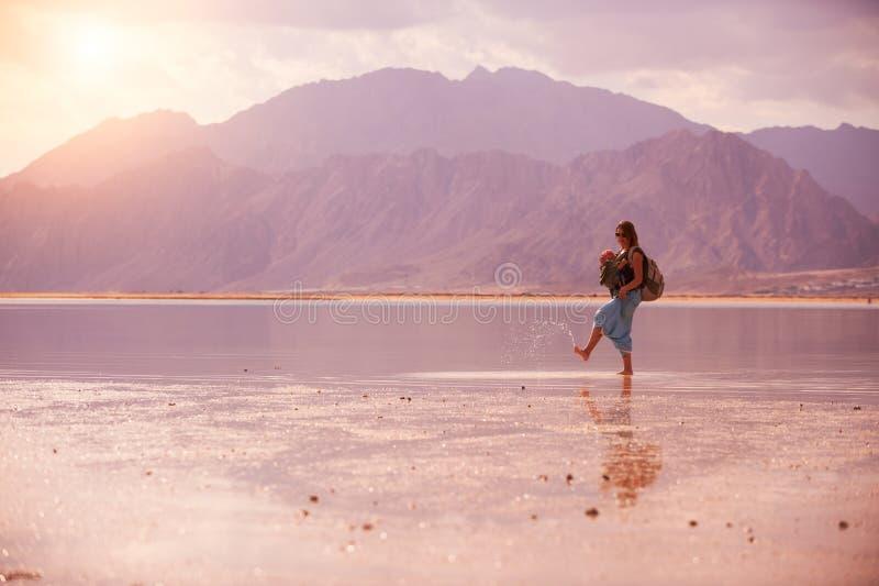 Una madre joven está viajando en la playa con su bebé en una honda fotos de archivo libres de regalías
