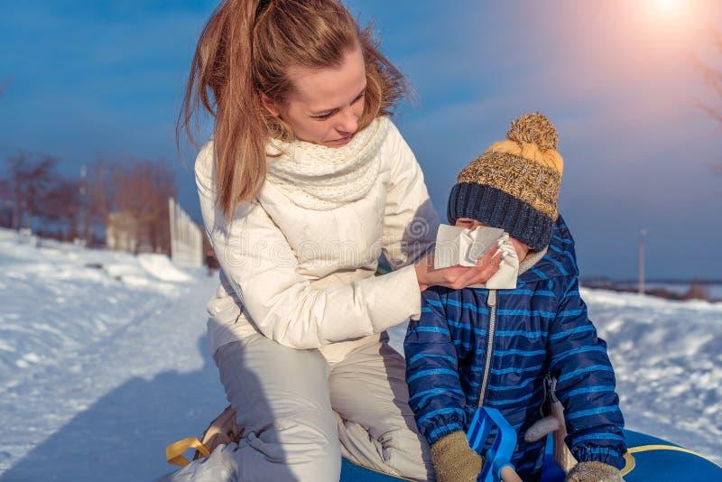 Una madre joven limpia su nariz con una servilleta a su pequeño hijo 3 años En invierno en la naturaleza en el parque reconstrucc fotografía de archivo