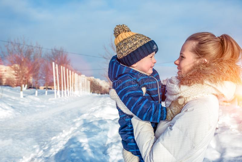Una madre joven, mujer con un niño, muchacho, hijo de 3 años, en el invierno afuera en la ropa caliente, jugando fotos de archivo libres de regalías