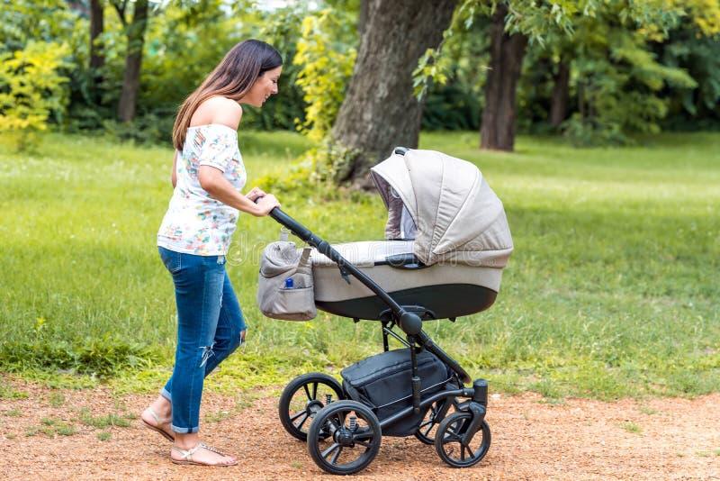 Una madre joven que camina con su bebé en un cochecito en el parque fotografía de archivo
