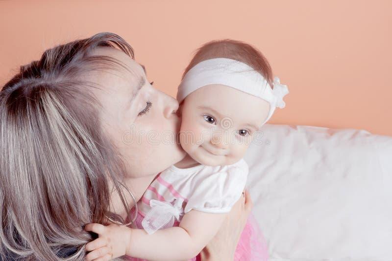 Una madre joven que celebra a su bebé lo besa. imagen de archivo libre de regalías