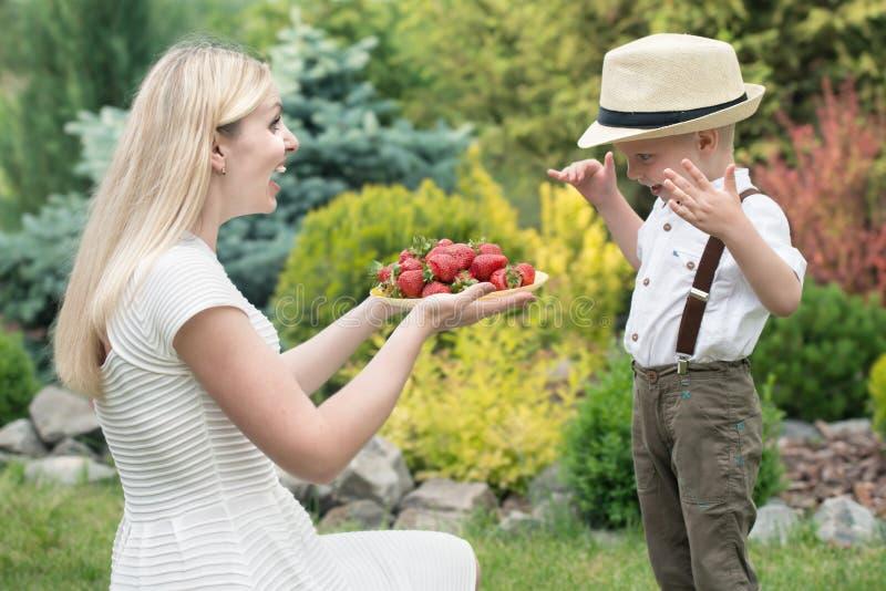Una madre joven trata sus fresas fragantes maduras del hijo del bebé fotografía de archivo