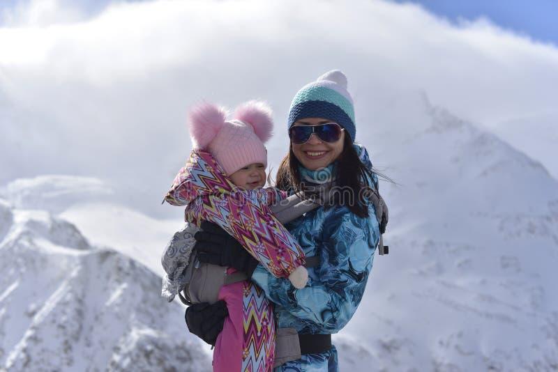 Una madre joven viaja en las montañas con su poca hija en un invierno soleado foto de archivo