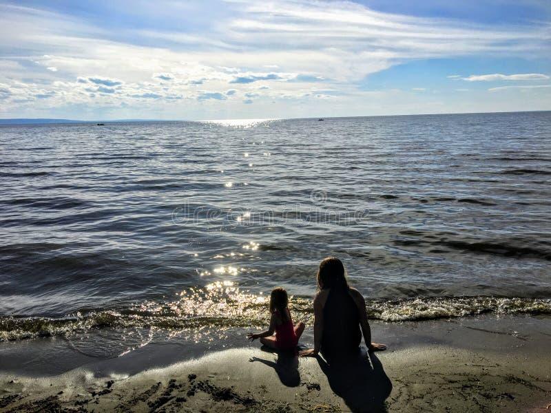 Una madre joven y su hija del niño que se sientan junto solamente en una playa arenosa que mira el agua chispeante del lago imagenes de archivo
