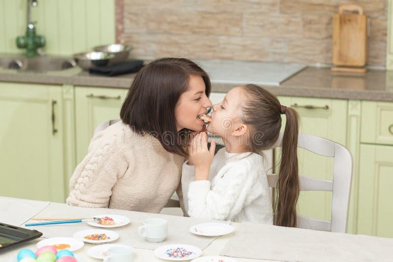 Una madre joven y sus galletas que intentan de la hija foto de archivo libre de regalías