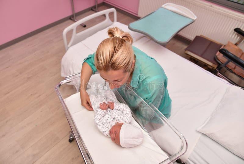 Una madre mira a su bebé recién nacido en el hospital fotos de archivo