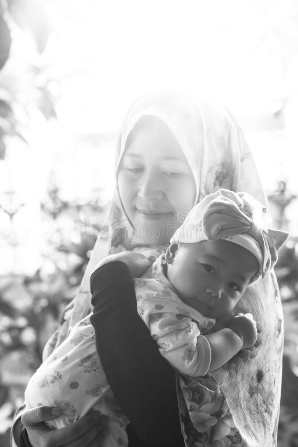 Una madre musulmana che tiene sua figlia del bambino fotografia stock