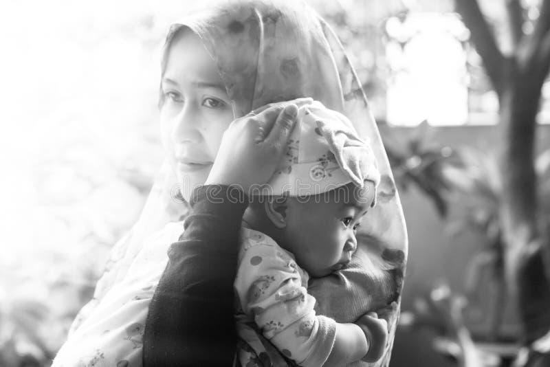 Una madre musulmana che tiene sua figlia del bambino immagine stock libera da diritti