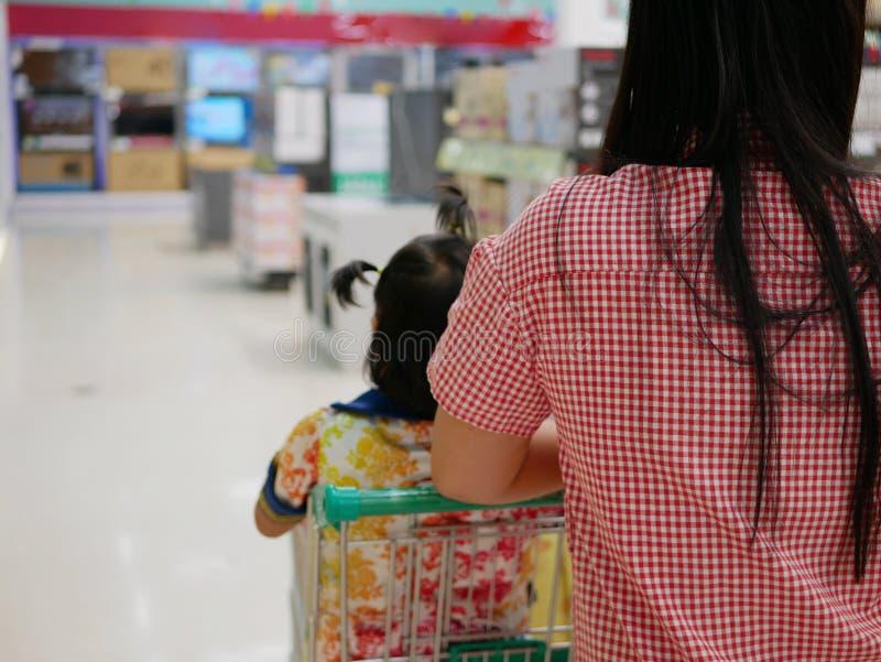 Una madre que hace las compras, empujando un carro de la compra, con su pequeño bebé, hija, dentro imagen de archivo