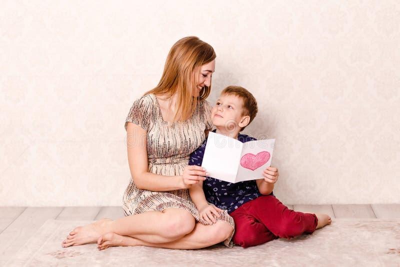 Una madre sonriente joven mira a su hijo de siete años que se sienta en la alfombra de la casa Tarjeta de felicitación para la ma fotografía de archivo