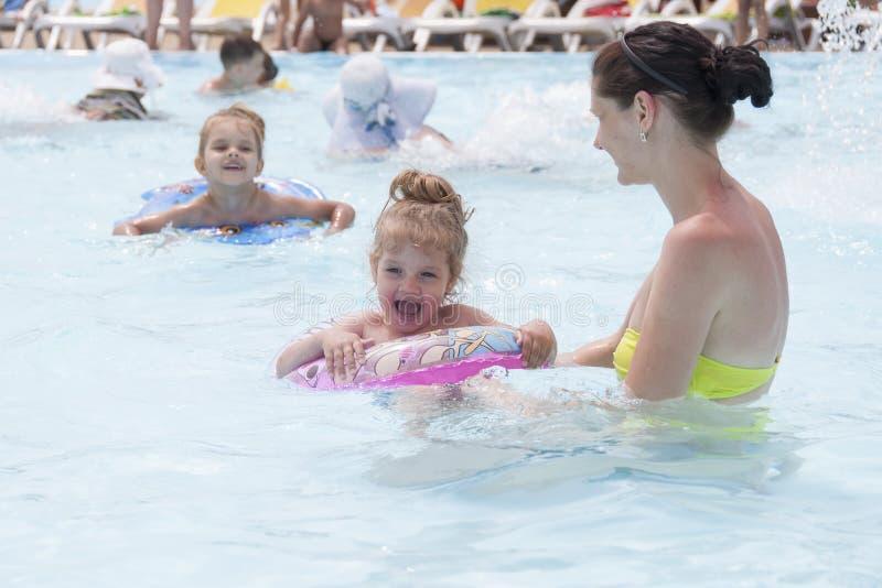 Una madre y dos hijas están nadando en una piscina pública imagen de archivo libre de regalías