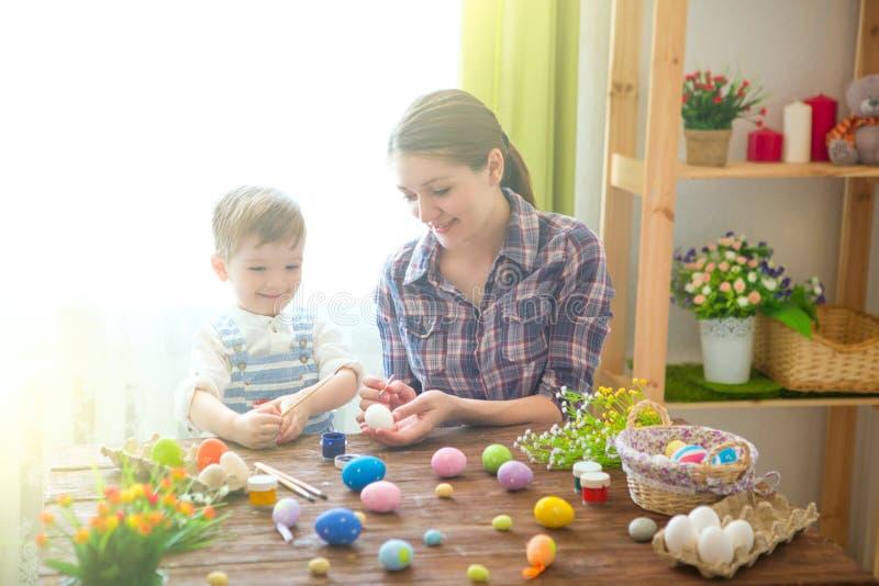 Una madre y su hijo que pintan los huevos de Pascua Familia feliz que se prepara para Pascua Pascua feliz foto de archivo libre de regalías