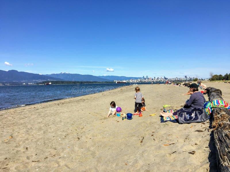 Una madre y tres ni?os en la playa que juega en la arena en un d?a soleado hermoso a lo largo de los bancos espa?oles foto de archivo libre de regalías