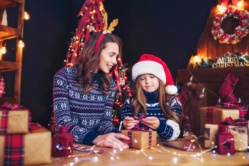 Una madre y un niño felices de la familia embalan los regalos de la Navidad fotos de archivo