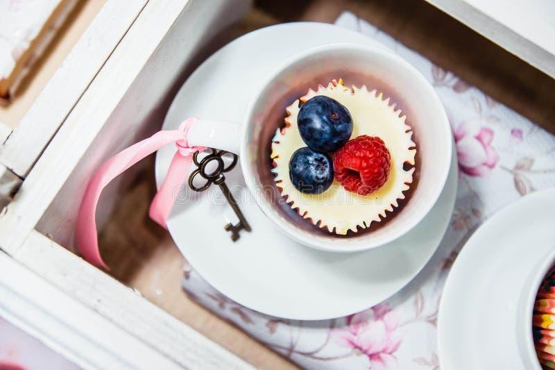 Una magdalena con los arándanos y la frambuesa en una taza fotografía de archivo libre de regalías