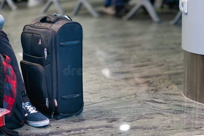 Una maleta se sienta al lado de un turista en un aeropuerto como la espera para subir a un avión en el aeropuerto internacional d imagen de archivo