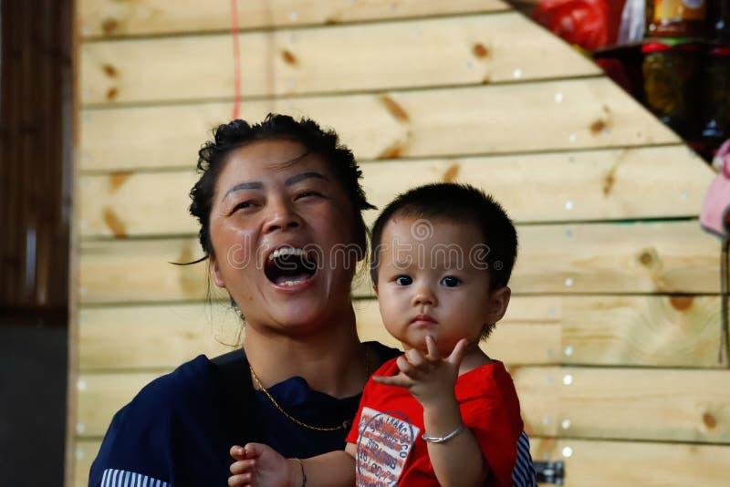 Una mamá sonriente con el bebé en un pueblo en Yunnan meridional, China Yunnan, China foto de archivo