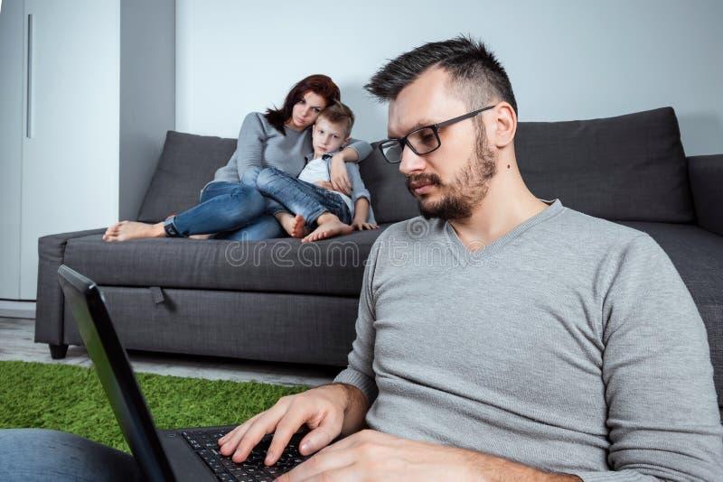 Una mamma e un figlio tristi stanno esaminando il loro padre, mentre il padre sta lavorando nei precedenti Il concetto trascura l immagini stock
