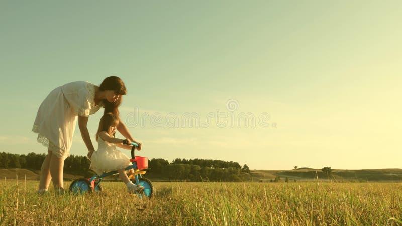 Una mamma felice insegna a una bambina che va in bici La mamma gioca con un bambino piccolo sul prato il bambino impara ad andare immagine stock