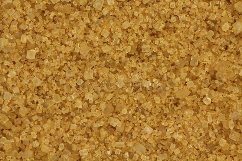 Una manciata di fondo della canna dello zucchero bruno immagine stock