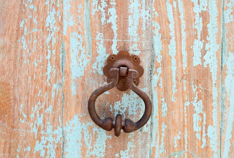 Una manija antigua del metal en una puerta de madera foto de archivo