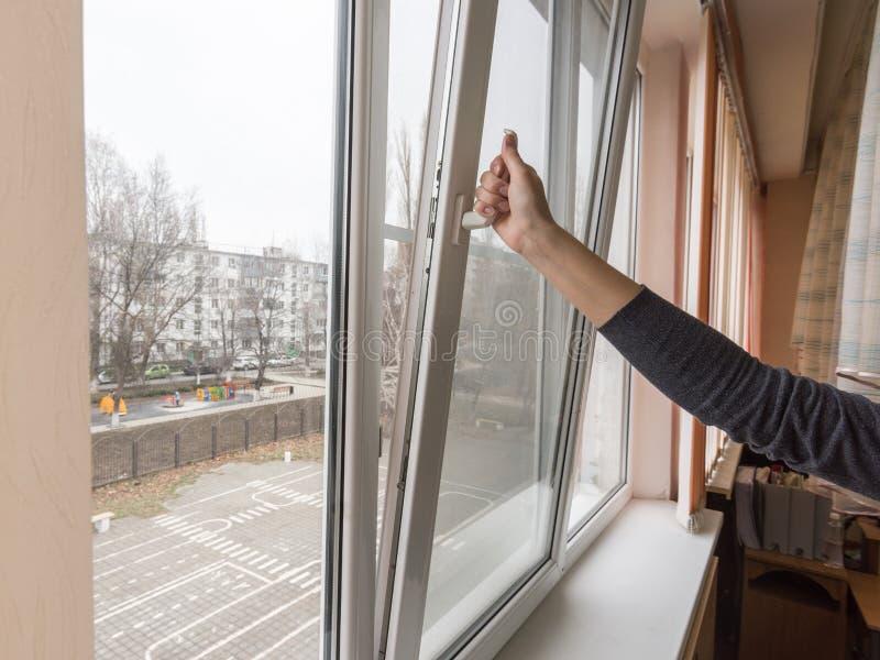 Una mano apre una finestra per ventilare la stanza immagine stock