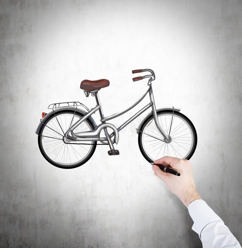 Una mano in camicia bianca convenzionale sta disegnando uno schizzo della bicicletta sul muro di cemento immagini stock