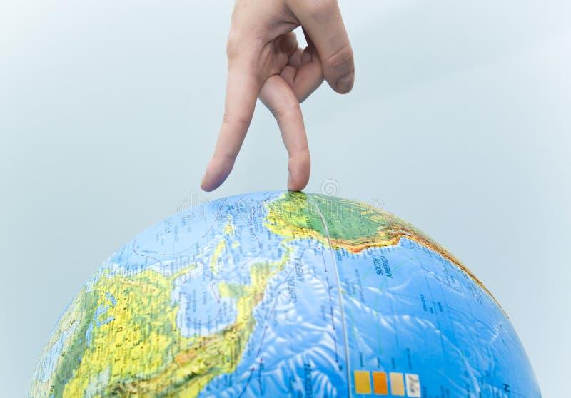 Una mano che cammina intorno ad un globo. fotografia stock libera da diritti