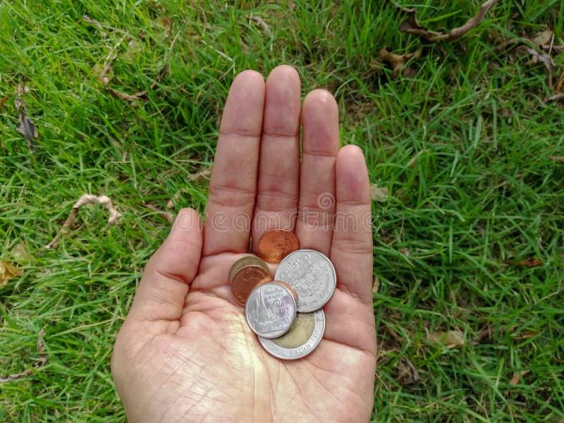 Una mano che giudica rimane monete, cinque, dieci, uno e venticinque monete allo zero assoluto di baht fotografia stock