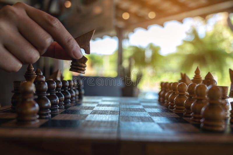 Una mano che tiene e che muove un cavallo nel gioco di legno della scacchiera fotografie stock libere da diritti
