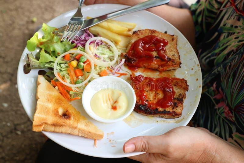 Una mano che tiene un piatto della bistecca della carne di maiale, pomodori, patatine fritte, cipolle, pane organico in un piatto fotografie stock