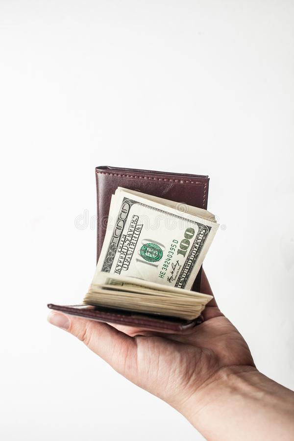 Una mano che tiene un portafoglio marrone in pieno di cento banconote in dollari isolate sopra un fondo bianco Copi lo spazio immagini stock