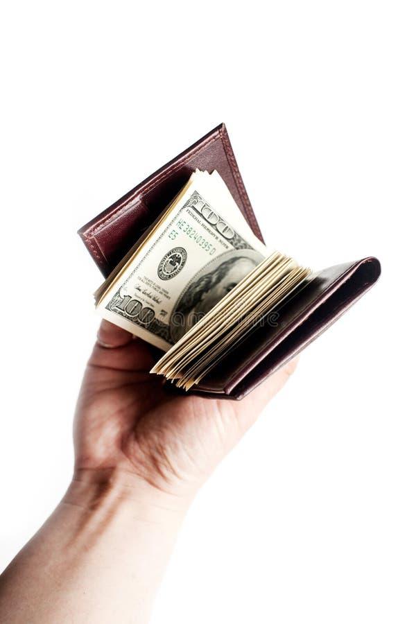 Una mano che tiene un portafoglio marrone in pieno di contanti isolati sopra un fondo bianco fotografia stock libera da diritti