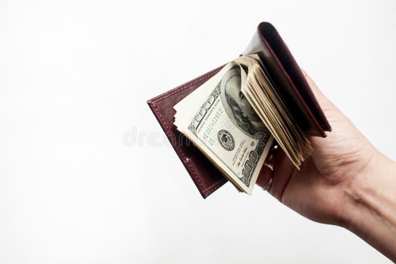 Una mano che tiene un portafoglio in pieno di cento banconote in dollari isolate sopra un fondo bianco Copi lo spazio immagine stock libera da diritti