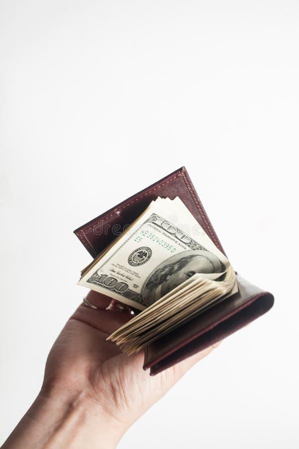 Una mano che tiene un portafoglio in pieno di cento banconote in dollari isolate sopra un fondo bianco verticale fotografia stock